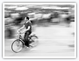 Man cycling past crowd